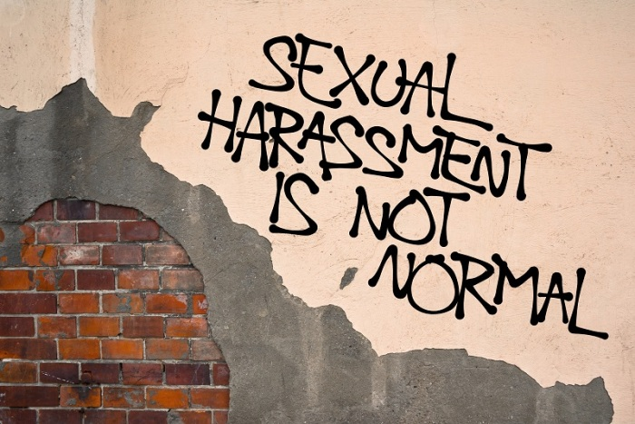 Sexual Harassment Is Not Normal - Handwritten graffiti sprayed on wall, anarchist aesthetics - appeal to resist and fight against sexually offensive behavior and verbal or physical assault